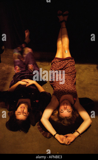 Two women relax lying upside down in a hall of Oakland Coleseum during the Grateful Dead s last Mardi Gras show - Stock Image