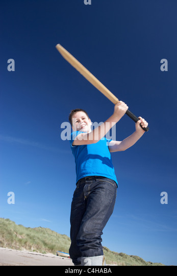 Boy playing cricket on beach - Stock Image
