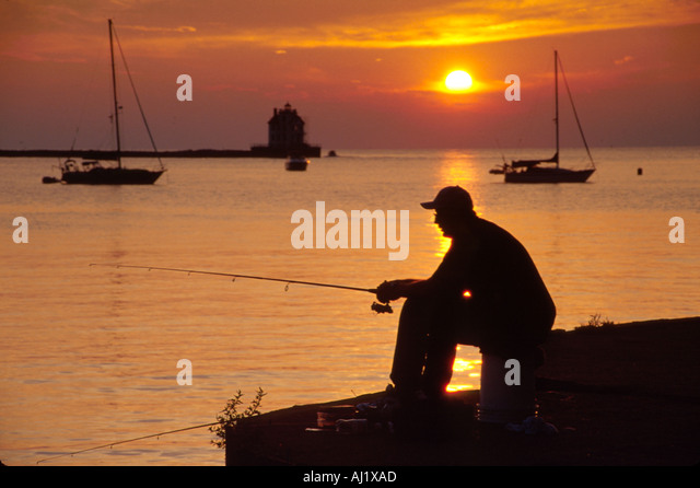 Ohio Lake Erie Lorain Lakeside Landing Marina sunset fishing Jewel of the Port Lighthouse beyond - Stock Image