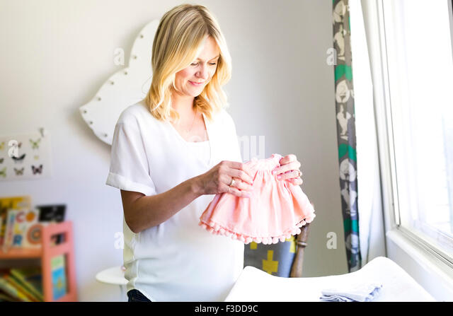 Pregnant woman holding baby clothing - Stock Image