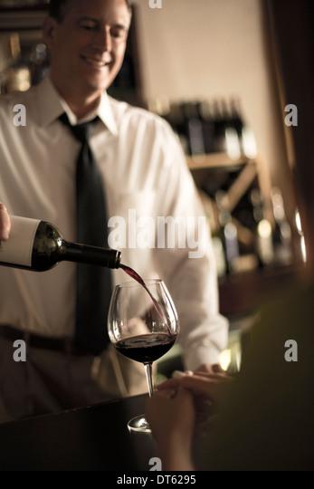 Bartender pouring red wine in bar - Stock-Bilder