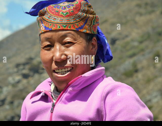 Closeup street portrait (outdoor headshot, three-quarter view) of a middle-aged Sherpa woman with traditional golden - Stock Image