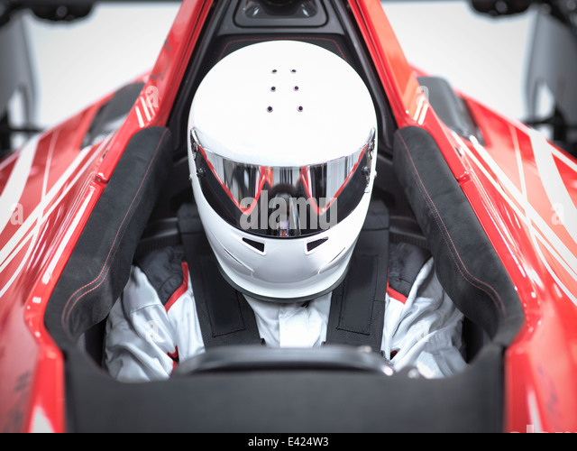 Racing driver wearing crash helmet in supercar - Stock Image