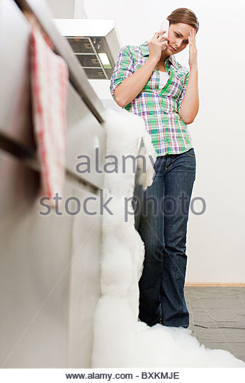 Young woman on phone with overflowing dishwasher - Stock Image