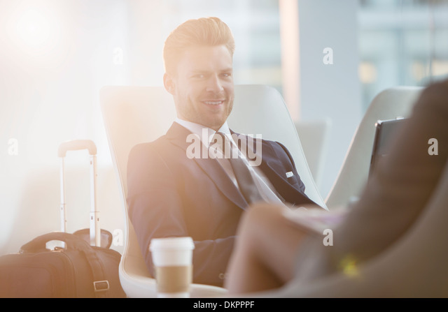Businessman smiling in airport - Stock Image