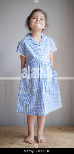 Young girl wearing uniform on first day of school - Stock Image