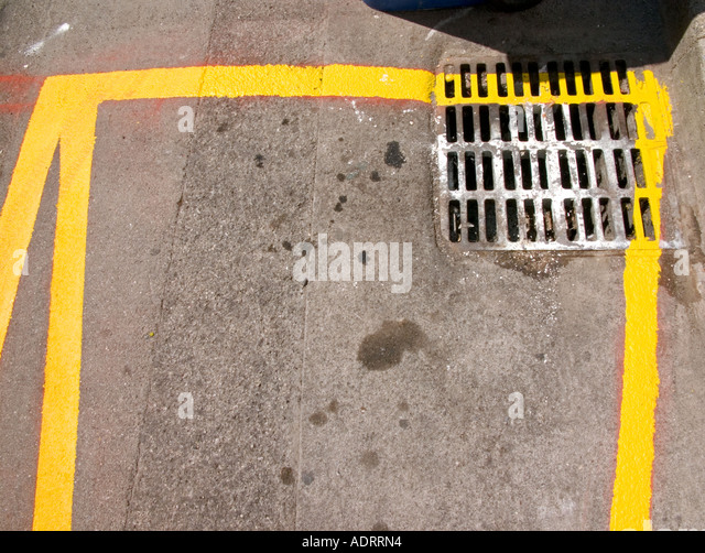 A detail of a freshly painted yellow road marking and a drain  from above - Stock Image
