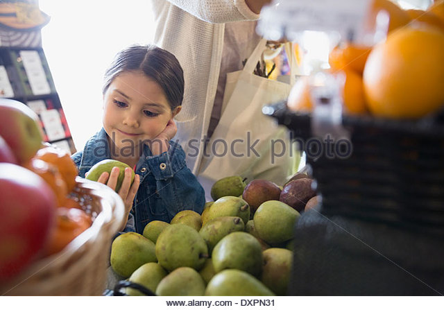 Girl looking at pear in market - Stock Image