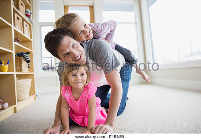 Father and daughters playing in living room - Stock-Bilder