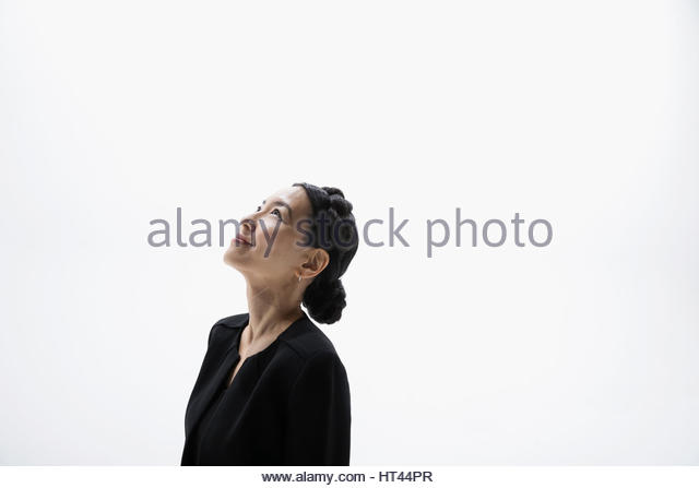Smiling businesswoman looking up against white background - Stock-Bilder
