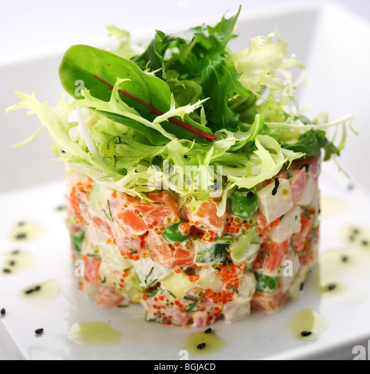 Salad with salmon, caviar and arugula on a white background - Stock Image