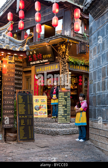 Waitresses touting for customers outside restaurant in Lijiang old town, Yunnan Province, China. JMH4758 - Stock Image