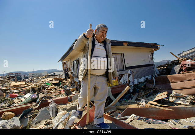 Katsunari Sasaki, 76, looks through the wreckage of his home - Stock Image
