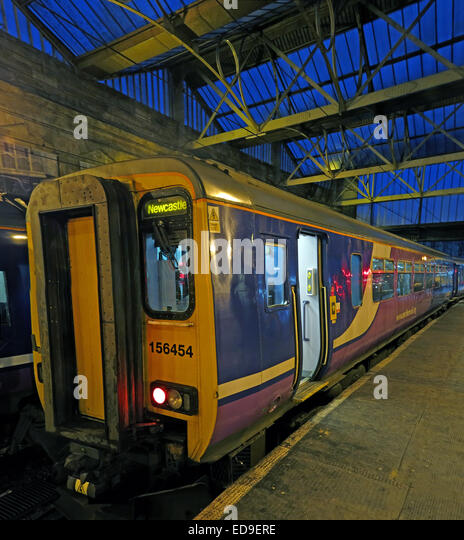 Newcastle train in Carlisle railway station at dusk, Northern England - Stock Image
