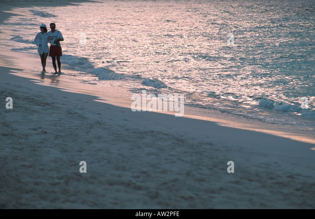 couple walking beach at twilight - Stock Image