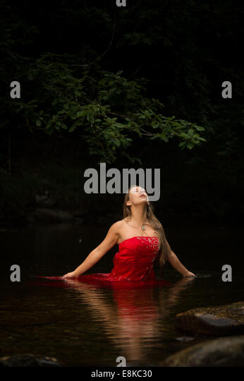 A blonde haired woman girl wearing a deep red frock ball gown up to her waist in water in a river with her eyes - Stock Image
