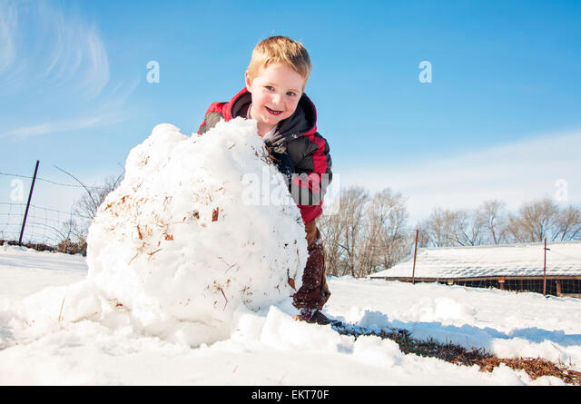 Child rolls large Snowball to make snowman - Stock-Bilder
