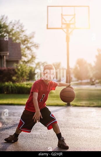 Portrait of young boy dribbling with basketball - Stock Image