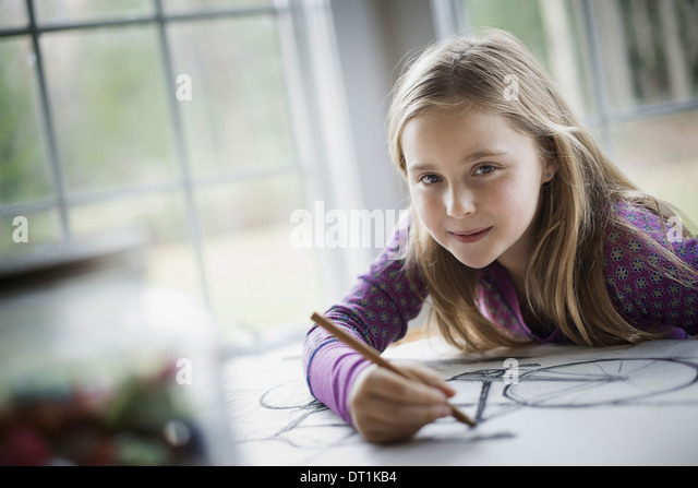 A family home A child sitting at a table using a pencil and creating a line drawing Artwork Drawing - Stock Image