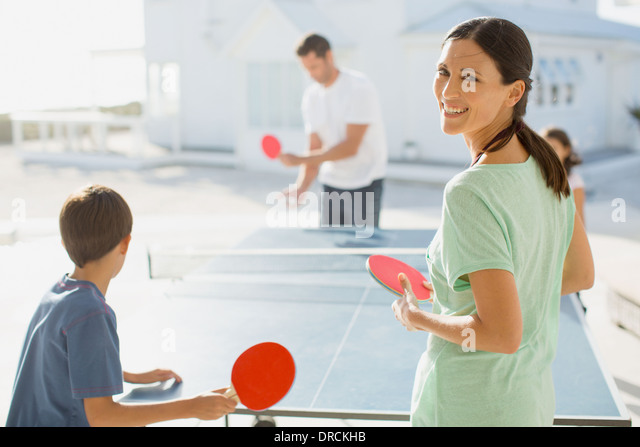 Family playing table tennis together outdoors - Stock Image