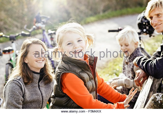 Girl on bike ride with family looking at camera smiling - Stock Image