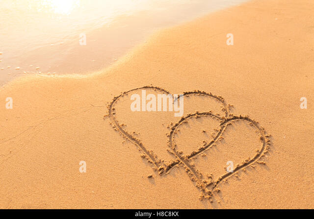 Shape of two hearts drawn in the sand of a tropical beach - symbol of love, honeymoon travel - Stock Image