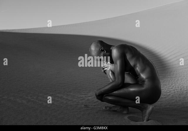 Nude woman crouching in desert - Stock Image