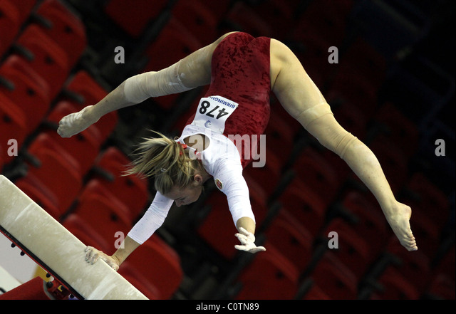 Female Gymnast performs a handstand using only one arm on beam at a gymnastics competition - Stock Image