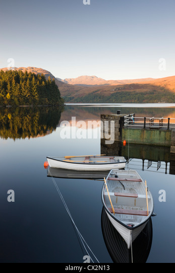 Rowing boats moored on Loch Katrine at Stronachlachar, Stirling, Scotland. Autumn (October) 2010. - Stock Image