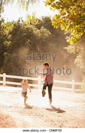 Father and son kicking up dust on dirt road - Stock Image