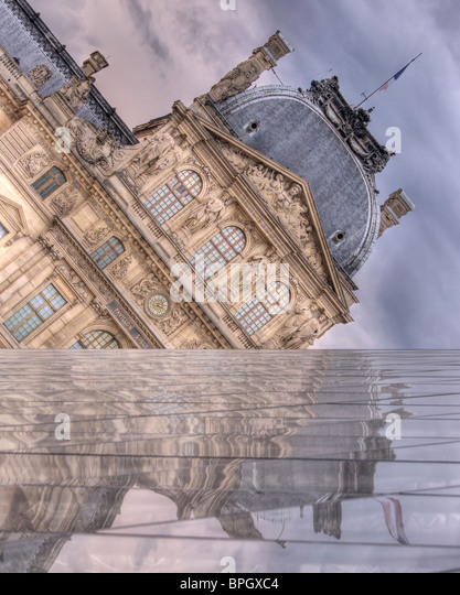 The Louvre reflects from I.M. Pei's Pyramid, as storm clouds gather above. One wall of the Pyramid forms a false - Stock Image