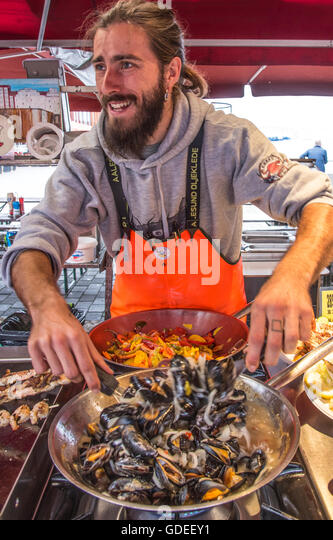 Happy fisherman cook preparing fresh Mussels from Sea at the Famous Bergen Fish Market, Bergen, Norway, Hordaland, - Stock Image