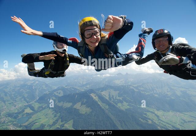 Woman on her first freefall jump with two instructors - Stock Image