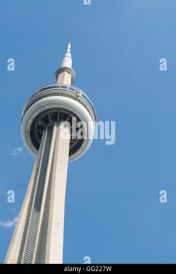 CN Tower Toronto against a blue sky with the tiny red specks of people completing the edge walk - Stock Image
