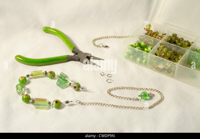 Beads of cane glass, Murano glass, and millefiori sparkle between sterling silver chains. - Stock Image