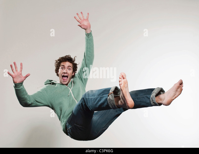 Man falling against grey background, mouth open, portrait - Stock Image
