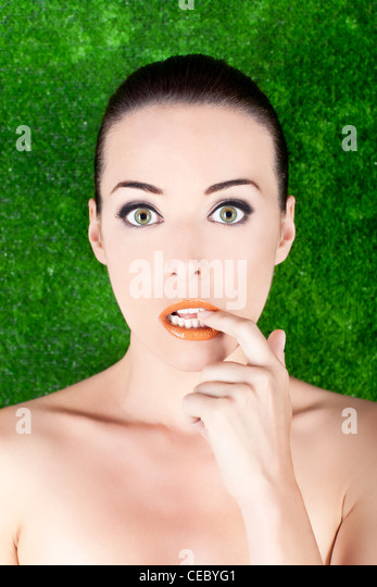 Closeup portrait of a beautiful nervous woman biting her finger isolated on green - Stock Image