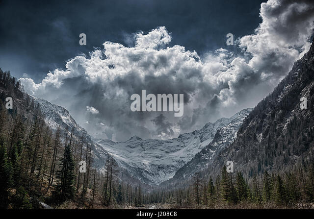 Storm clouds over the glacier in spring season with forest in foreground - Stock Image