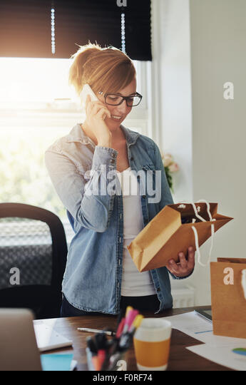 Smiling attractive young female entrepreneur standing in her home office taking orders over the phone for products - Stock-Bilder