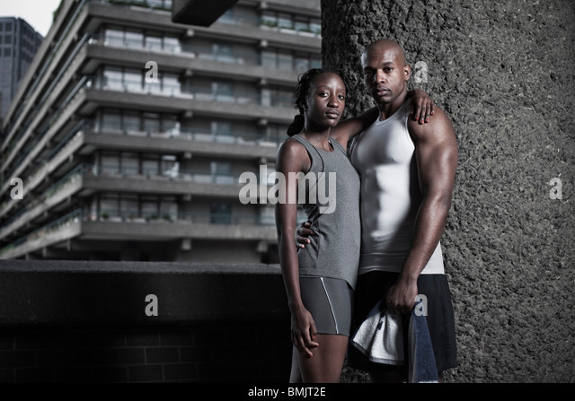 Portrait of athletic man and woman dressed in sportswear on city housing estate - Stock-Bilder