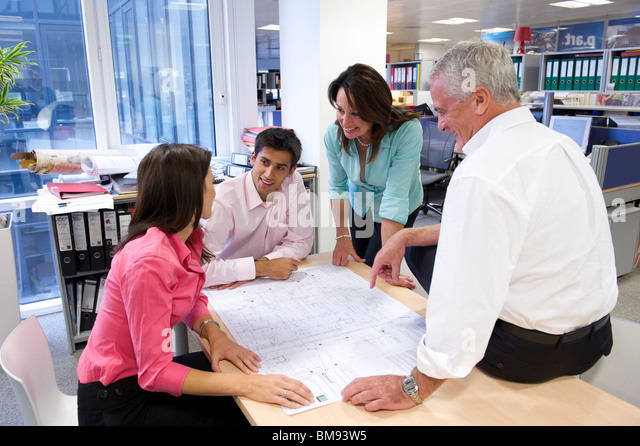 Team discussing architectural plans in office - Stock-Bilder