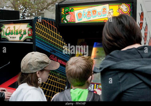 Children playing Dig Dug arcade video game - USA - Stock Image