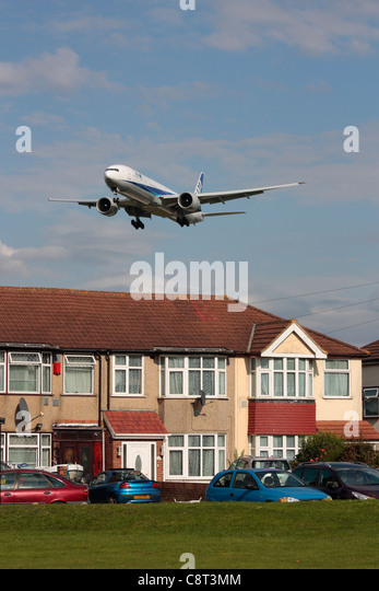 ANA Boeing 777-300ER overflying a residential area on approach to Heathrow Airport - Stock Image