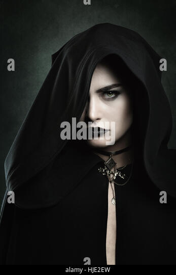 Dark portrait of a beautiful vampire woman with black hood . Halloween and horror concept - Stock-Bilder