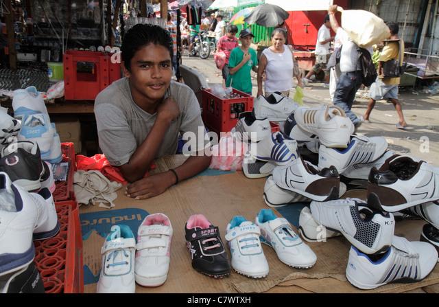 Managua Nicaragua Mercado Oriental flea market marketplace shopping shopper vendor stall Hispanic boy teen job athletic - Stock Image