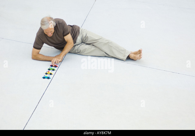 Mature man sitting on the ground, lining up toy cars, high angle view - Stock Image
