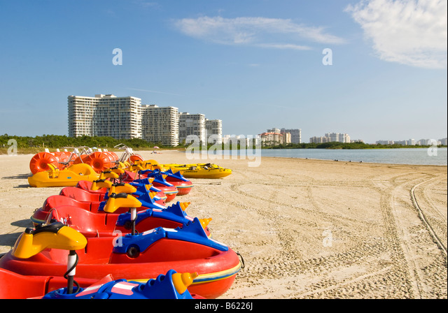 Tiger Tail Beach Marco Island Florida brightly colored red boats high rise condominiums in the background - Stock Image