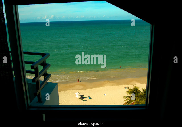 San Juan Puerto Rico Isla Verde beach with sunbathers, blue sky viewed through or framed by a resort hotel room - Stock Image