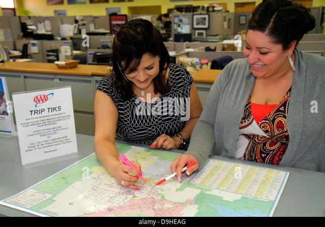 Nevada Las Vegas AAA American Automobile Association Hispanic woman coworkers map job counter smiling - Stock Image