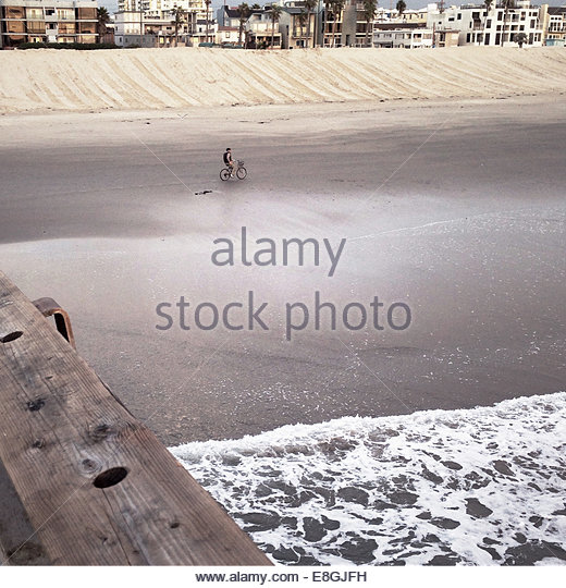 Man cycling on beach - Stock Image
